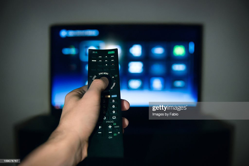 Male hand using Tv remote control : Foto de stock