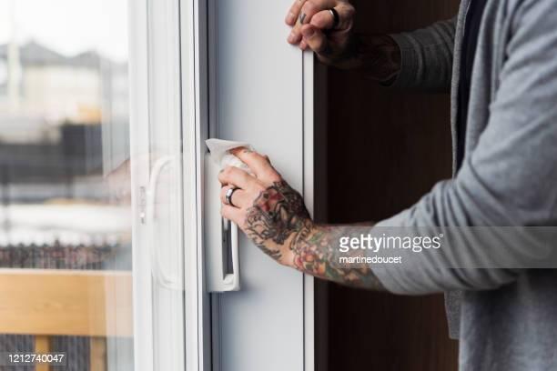 """mano maschile con tatuaggi che pulivano la maniglia della porta del patio. - """"martine doucet"""" or martinedoucet foto e immagini stock"""