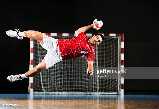 male handball player in action. - scoring a goal stock pictures, royalty-free photos & images