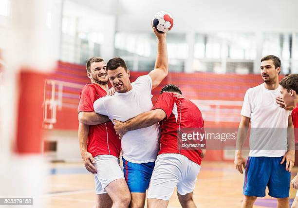 Male handball players in action.