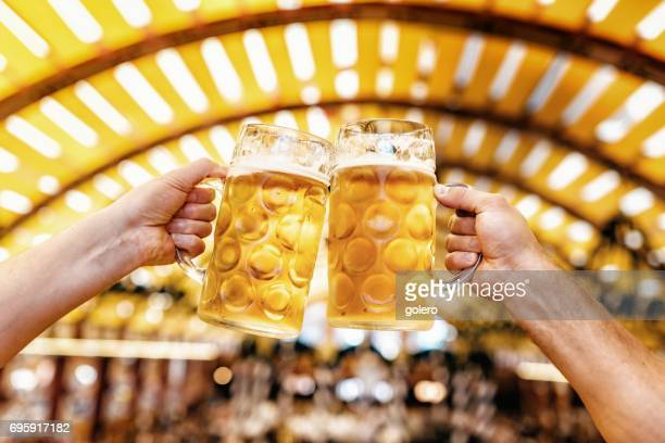 male hands clinking beer glasses at oktoberfest in munich