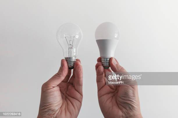 male hands compare an incandescent light bulb and a led lamp - comparison stock pictures, royalty-free photos & images