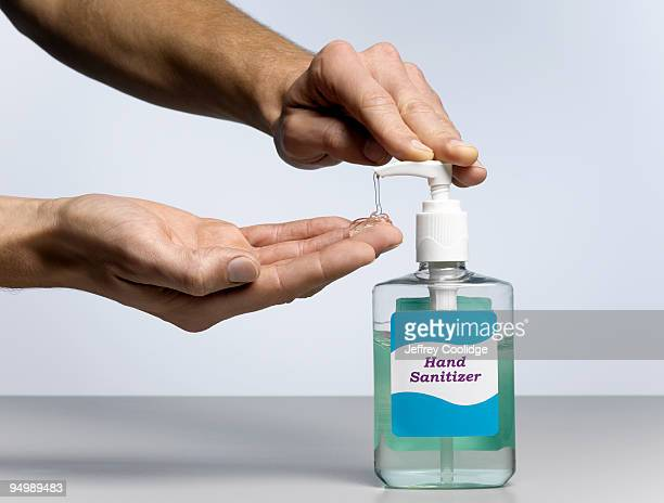 male hands dispensing hand sanitizer - hand sanitizer stock pictures, royalty-free photos & images