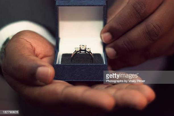 male hands holding engagement ring in box - engagement ring box stock photos and pictures