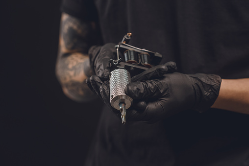 Male hands in gloves holding tattoo machine isolated on black 936428676