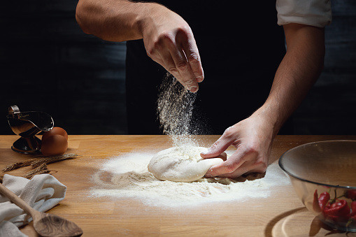 Male hands kneading dough 680190942
