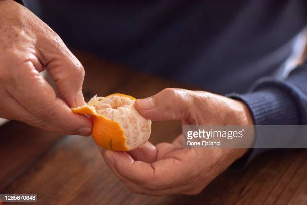 male hands peeling a mandarine - dorte fjalland stock pictures, royalty-free photos & images