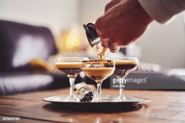 male hands pouring espresso martini cocktail into glass - espresso stock photos and pictures