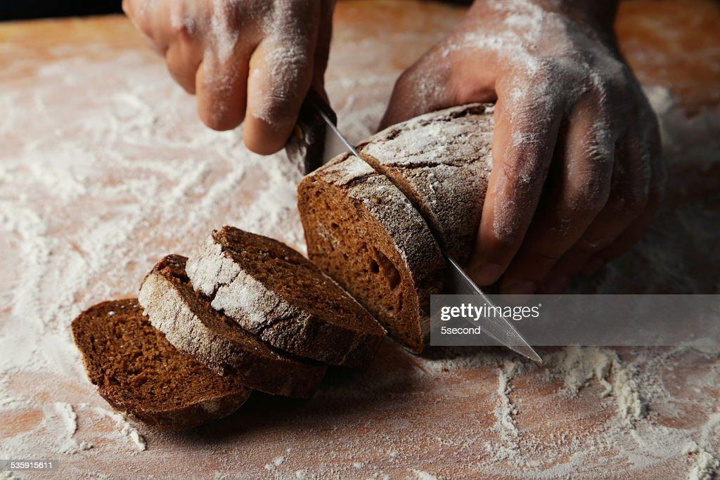 Macho mãos corte fresco Pão : Foto de stock