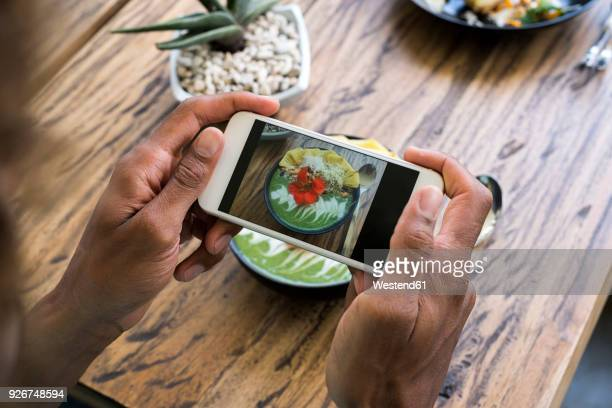 male hands taking a picture of smoothie bowl with smartphone - influencer stock pictures, royalty-free photos & images