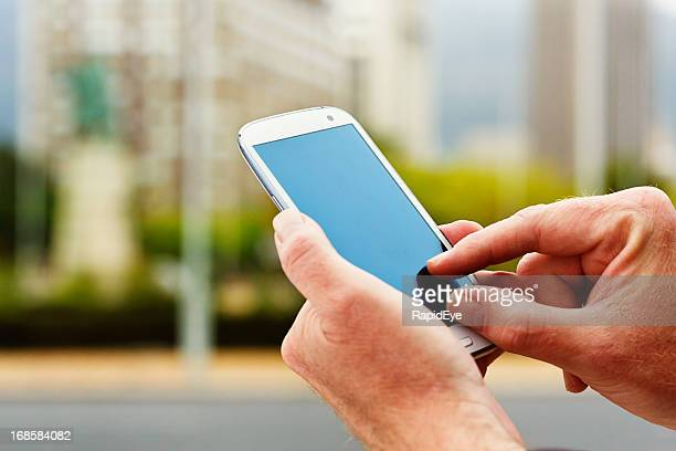 Male hands tap smart phone screen in city setting