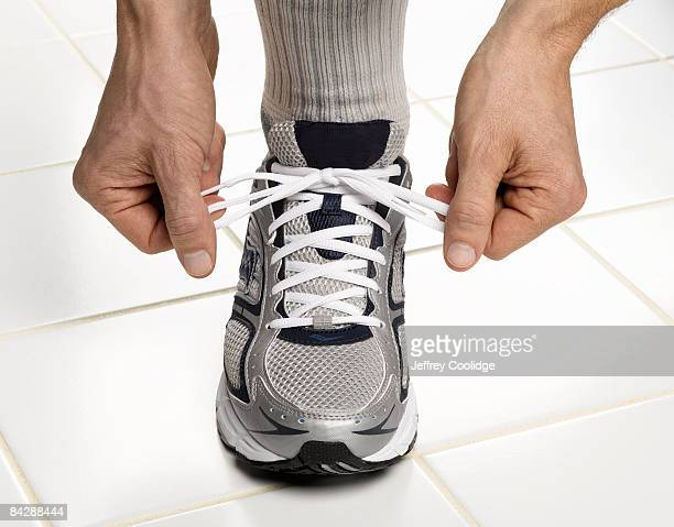 male hands tying sneaker lace