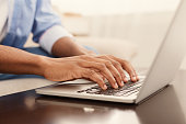 Male hands typing text or programming code on laptop