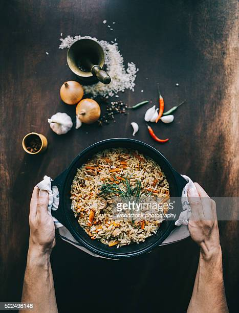 Male hands with bowl of Pilaf with pork over the aged wooden table.