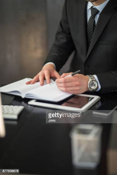 male hands writing plans in notepad - mission statement stock photos and pictures