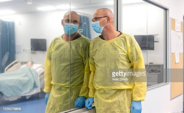 male health care worker looking upset as he looks through a window into a room with a hospital bed - essential workers stock pictures, royalty-free photos & images