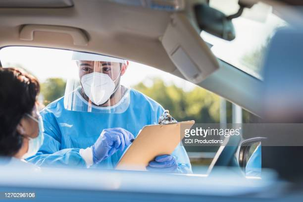 男性医療従事者は、女性にcovidテストを説明します - ドライブスルー検査 ストックフォトと画像