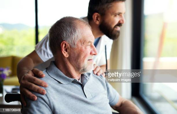 a male healthcare worker talking to senior man in wheelchair indoors at home. - gezondheidszorg beroep stockfoto's en -beelden