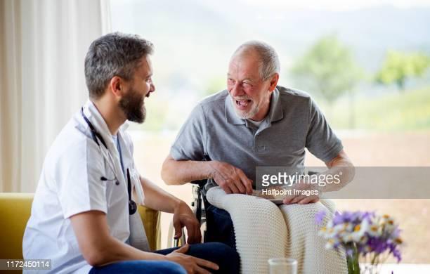 a male healthcare worker talking to senior man in wheelchair indoors at home, laughing. - pessoas com deficiência imagens e fotografias de stock