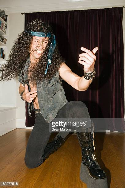Male heavy metal musician playing air guitar