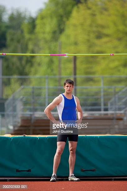 Male high jumper in front of high jump pit, portrait