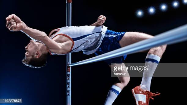 male high jumper jumping over bar - high jump stock pictures, royalty-free photos & images