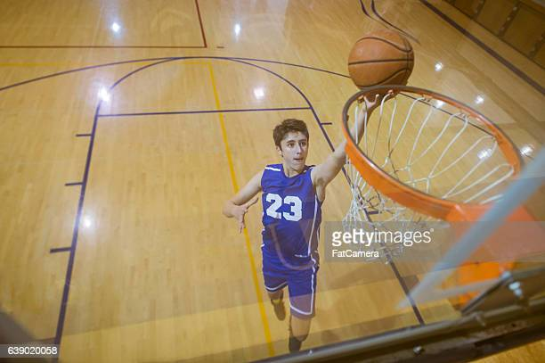 A male high school basketball player rises to the