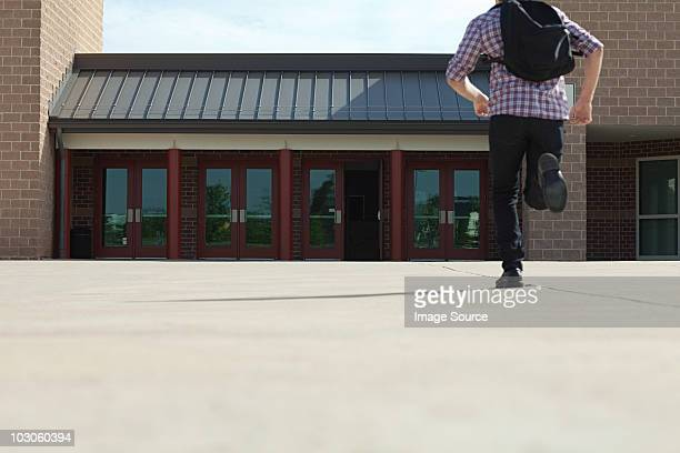 male high school student running toward school - beat the clock stock photos and pictures