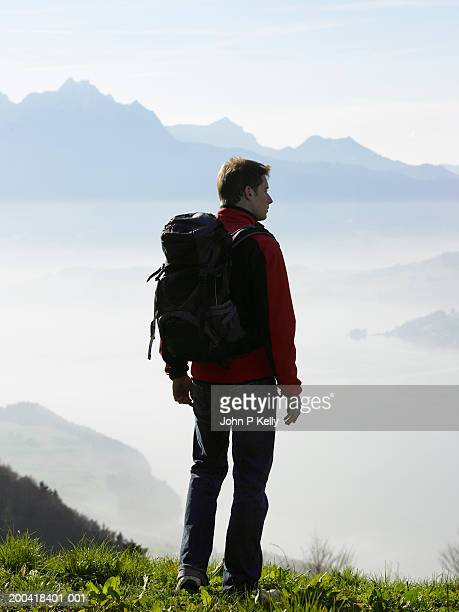 Male hiker above clouds looking at scenic, rear view