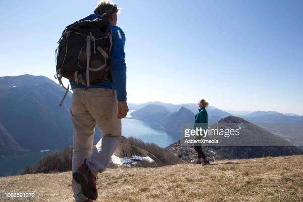 山の上の頂上に女性ハイカーに近づく男性ハイカー - スイス ルガーノ ストックフォトと画像
