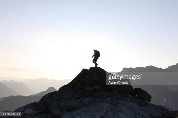 male hiker ascends to mountain summit, sunrise - ascent xmedia stock pictures, royalty-free photos & images
