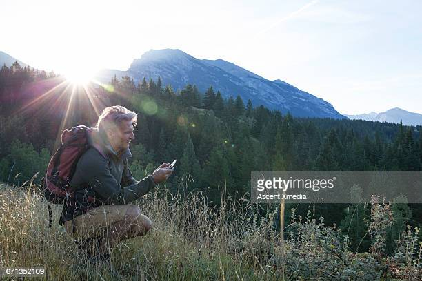 Male hiker checks smart phone for direction, mtns