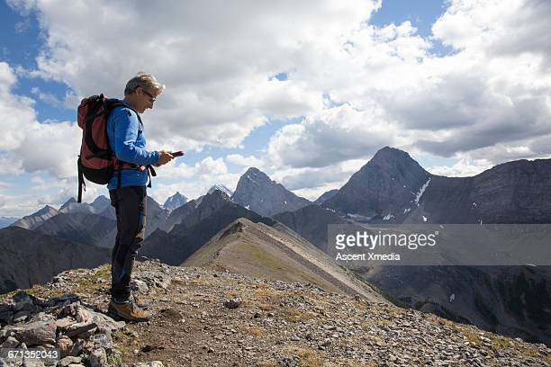 Male hiker checks tablet for direction, mtns