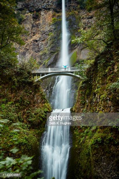 male hiker crossing footbridge over multnomah falls, oregon, usa - columbia river gorge stock pictures, royalty-free photos & images