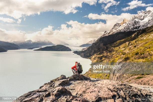male hiker crouching to look out over grey lake and glacier, torres del paine national park, chile - patagonia chile stock photos and pictures