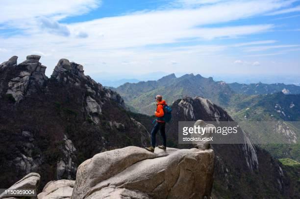 excursionista masculino disfrutando de la belleza naturalezas en el parque nacional bukhansan, corea - parque nacional fotografías e imágenes de stock