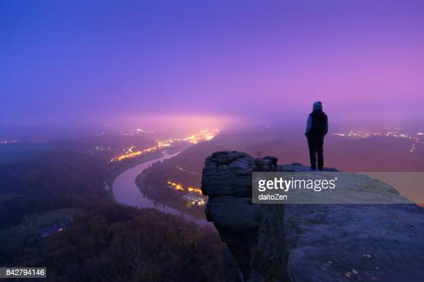 Male hiker enjoying scenic view over Elbe river landscape from Lilienstein viewpoint, Nationalpark Sächsische Schweiz, Saxon Switzerland, Saxony, Germany