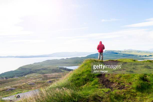 Male hiker enjoying view of landscape in Scottish Highlands.