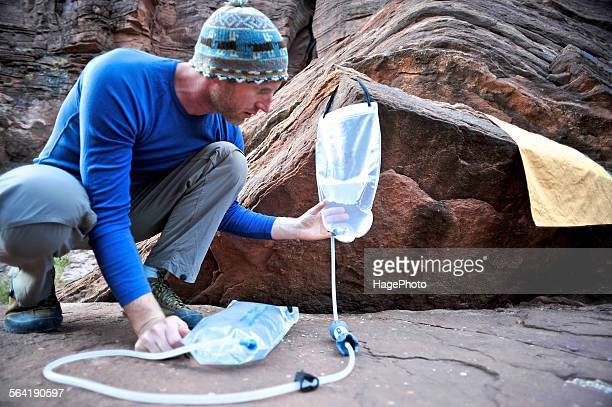 Male hiker filters water on a cliff-pinched patio near Deer Creek Falls in the Grand Canyon outside of Fredonia, Arizona November 2011.