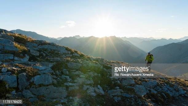 male hiker follows mountain ridge above ranges - ascent xmedia stock pictures, royalty-free photos & images