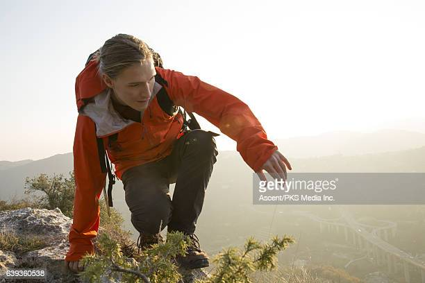 Male hiker follows route along cliff edge, valley below