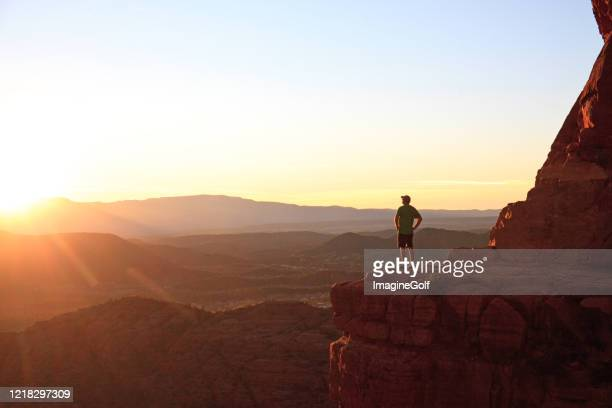 male hiker in sedona at dramatic viewpoint at sunset - só um homem maduro imagens e fotografias de stock