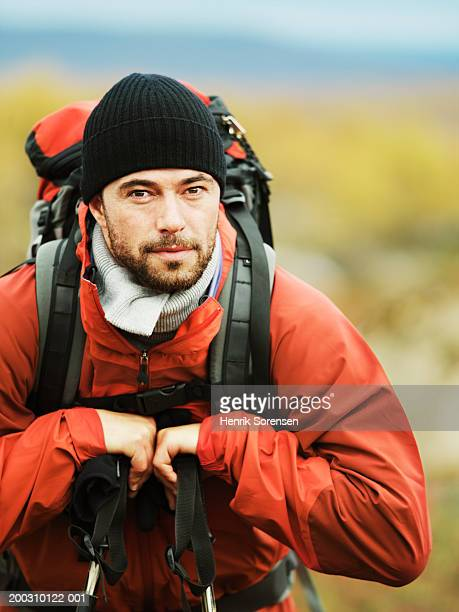 Male hiker leaning on hiking poles, portrait