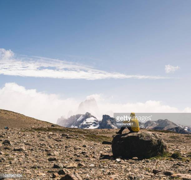 male hiker looking at landscape against sky while sitting on rock, patagonia, argentina - argentina stock pictures, royalty-free photos & images