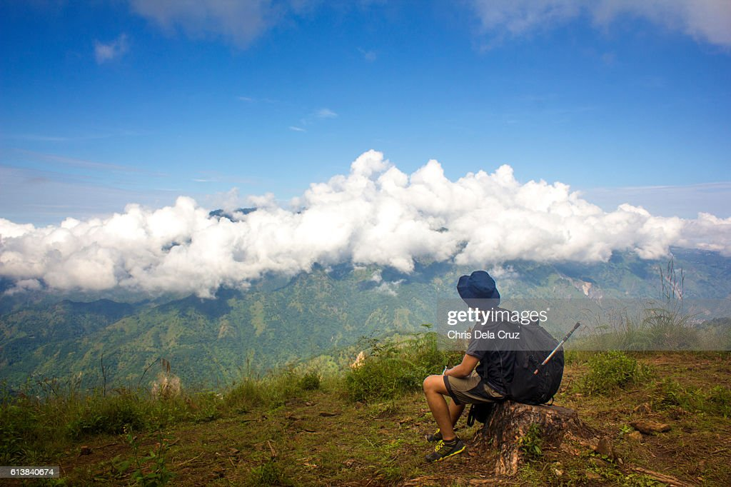 Male hiker looking at the clouds over mountain : Stock Photo