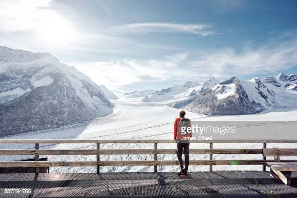 Male hiker looking out at glacier and snowy peaks, Aletsch Glacier, Switzerland