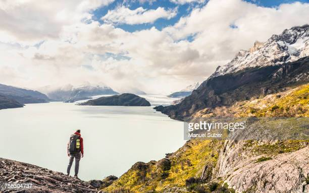 Male hiker looking out over Grey Lake and Glacier, Torres del Paine national park, Chile