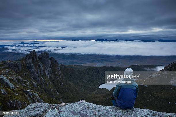 A male hiker looking out over South West Tasmania from the Western Arthur range, South West National Park, Tasmania, Australia