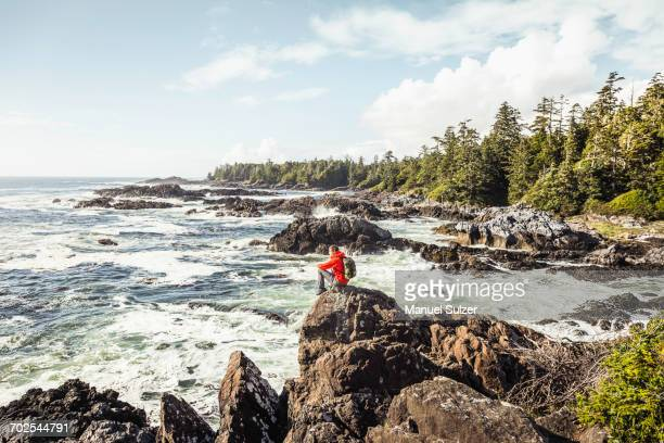 Male hiker looking out to sea from rocky coast, Wild Pacific Trail, Vancouver Island, British Columbia, Canada