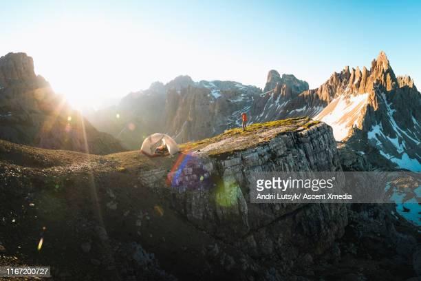 male hiker looks off from ridgetop campsite - キャンプ 1人 ストックフォトと画像